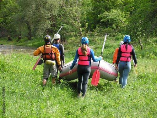 rafting team carrying the boat on the river-bank poster