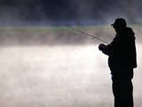 trout fisherman by a misty lake poster