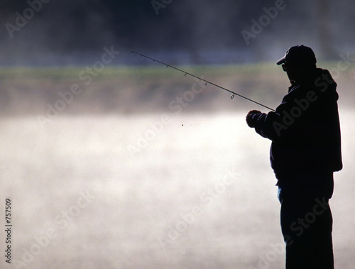 trout fisherman by a misty lake