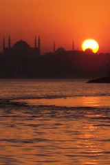 sun behind mosques