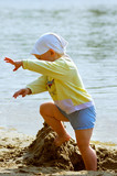 baby girl playing on the sea shore poster