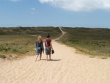 girls walk sandy beach path poster