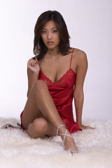 sexy young asian woman in red lingerie seated