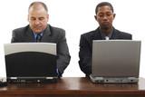 businessmen at desk with laptops poster