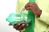 businessman putting one dollar bill in green piggy