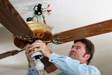 electrician removes ceiling fan poster