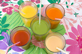 five glasses of various juices with straws poster