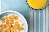 plate of breakfast cereal and glass of orange juic poster