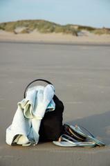 sac, serviette et tongue sur le sable