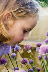 young girl smelling purple flowers.