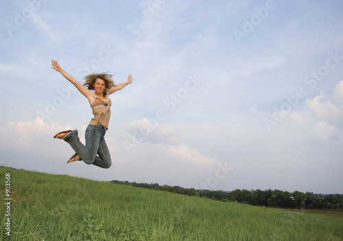 pretty girl leaping in field