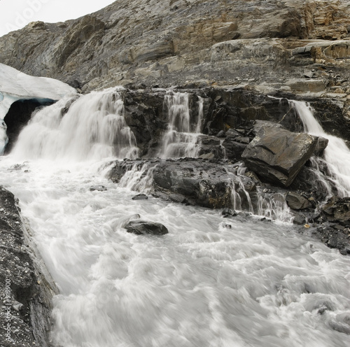 canvas print picture muddy river with waterfall flowing from below the