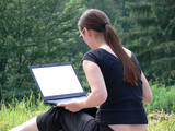 a girl sitting outside with a laptop poster