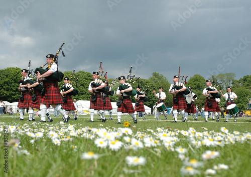 Leinwanddruck Bild scottish pipe band marching on the grass