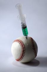 baseball and syringe on a light background