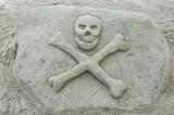 sand sculpture of a skull & crossbones poster