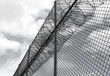 angle view of prison fence with razor wire