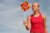 young woman blowing pinwheel poster