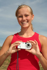 happy young woman holding digital camera