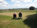 elderly couple relaxing in wheelchairs in the sun poster