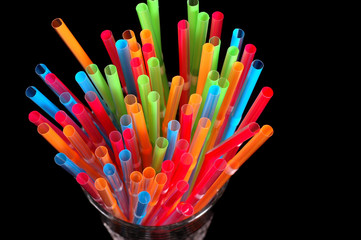 close-up of colorful straws in clear glass
