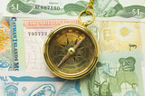 old style gold compass with chain on money backgro poster