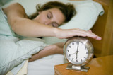 young woman in bed turining off alarm clock poster