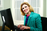 beautiful business woman smiling and typing on computer poster