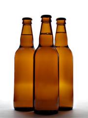 three beer bottles in backlight