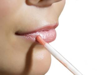 the woman puts lipstick on lips