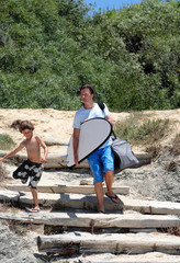 man and his son arriving at the beach to surf