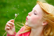 young teenager blowing a dandelion