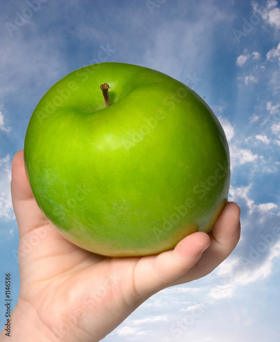 hand of child holding a green apple on sky backgro
