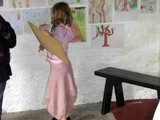 girl with her painting & looking at other painting poster