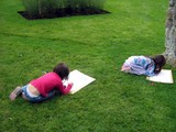 girls sitting on the grass drawing poster