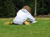 a girl sitting on the grass drawing poster