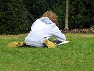 a girl sitting on the grass drawing