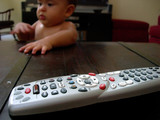 baby and remote control poster