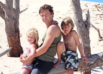 man sitting on a log with his son and daughter