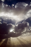 sun rays behind clouds after a storm poster