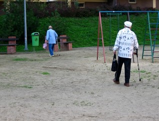 elderly woman and man walk on crutches