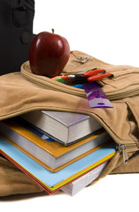 brown school back pack full of school supplies and an apple