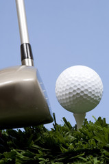 golf ball on tee on grass with driver
