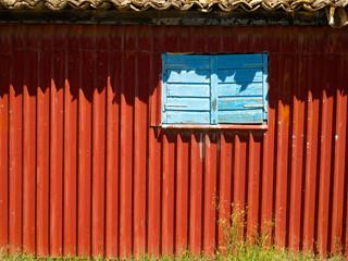 red building, blue shutters, green grass