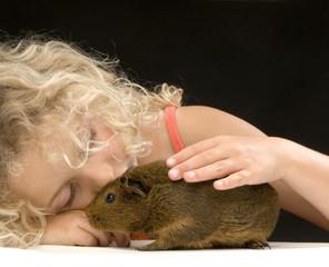 jeune fille caressant un cochon d'inde