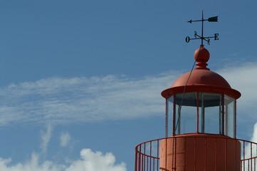 un beau phare rouge avec sa belle girouette