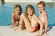 trois enfants au bord de la piscine