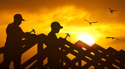 two roofer hammering