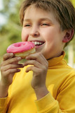 child eating a pink doughnut poster