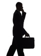silhouette of walking man with suitcase and cell